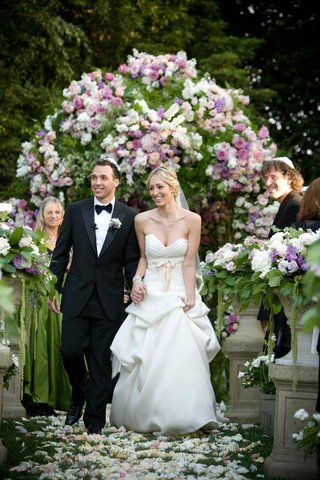 bride-and-groom-exit-backyard-holding-hands
