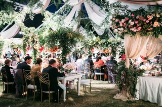 wedding reception guests and family at tables sweetheart table flower arbor drapery greenery