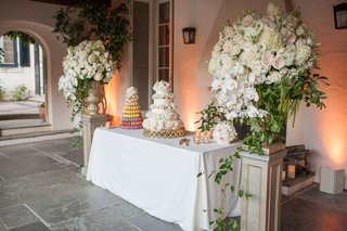 dessert-table-tower-of-macarons-white-cake-flowers-flanked-by-tall-white-green-floral-arrangements