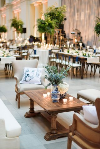 wedding-reception-lounge-wood-coffee-table-upholstered-chair-sofa-blue-white-vase-eucalyptus