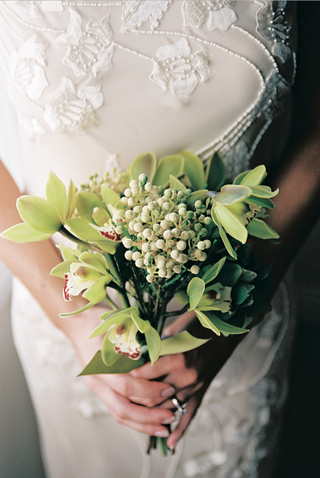 bride-in-beaded-gown-holds-green-flower-bouquet