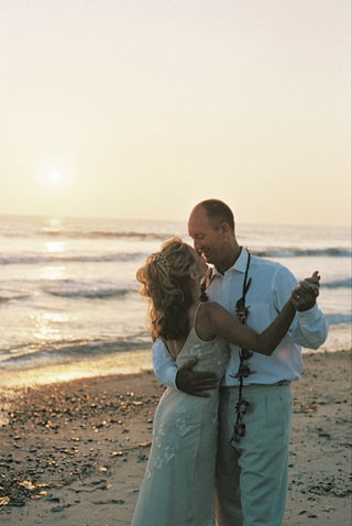 bride-and-groom-dance-together-on-sand-with-sunset-in-background