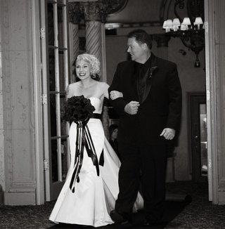 black-and-white-photo-of-bride-in-an-alvina-valenta-gown-being-escorted-to-ceremony