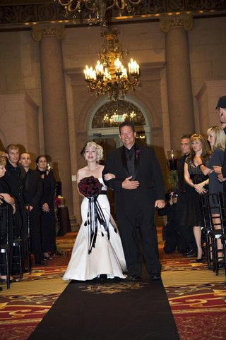 bride-in-a-strapless-alvina-valenta-gown-and-black-sash-walks-down-the-aisle-with-father