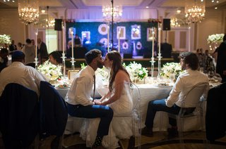 a-newlywed-couple-sitting-in-ghost-chairs-at-head-table-share-a-kiss
