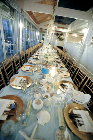 long-wedding-reception-table-with-gold-place-settings-and-seashells