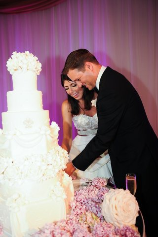 bride-and-groom-cut-ivory-wedding-cake-with-purple-lighting