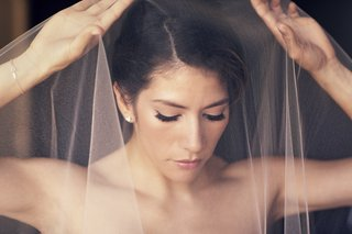 bride-putting-mantilla-veil-over-head-and-face
