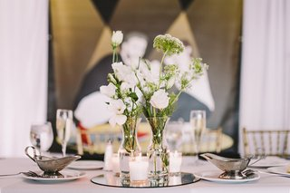 simple-reception-centerpieces-white-flowers-in-bud-vases-on-mirror-with-candles