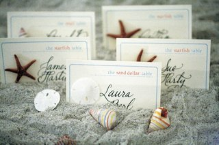 escort-cards-in-sand-decorated-with-seashells