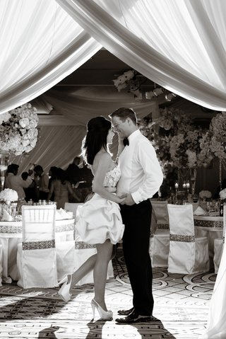 black-and-white-photo-of-bride-popping-foot-as-she-kisses-groom