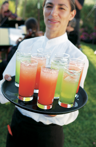 waitress-holds-tray-of-brightly-colored-signature-cocktails