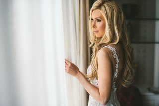 bride-with-long-blonde-hair-low-back-illusion-wedding-dress-dimitras-bridal-couture-looking-window