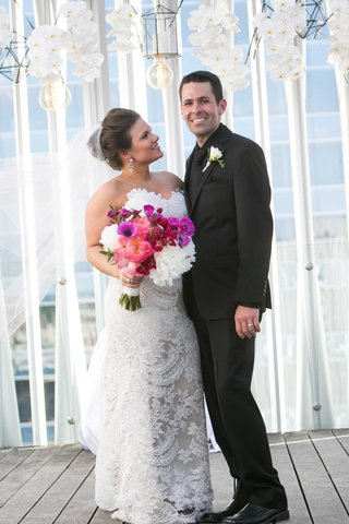 bride-fit-flare-lace-gown-holding-bouquet-pink-purple-white-flowers-looks-at-groom-black-tuxedo