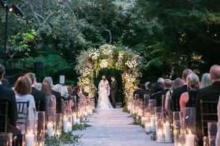 bride-and-groom-under-greenery-arch-hotel-bel-air-candles-lining-aisle-with-greenery