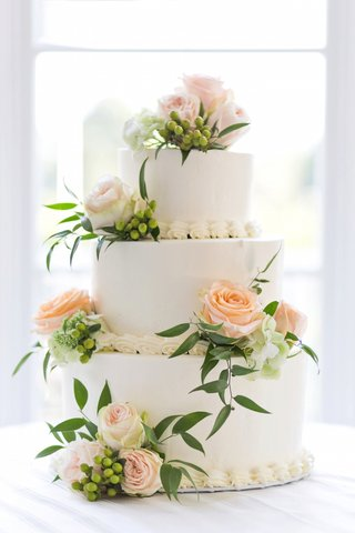 three-layer-white-wedding-cake-with-pastel-orange-roses-green-hydrangea-sprigs-and-greenery