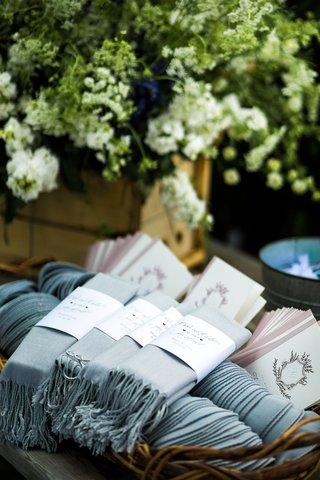 wedding-ceremony-favors-ceremony-programs-and-custom-labels-on-light-blue-pashmina-shawl