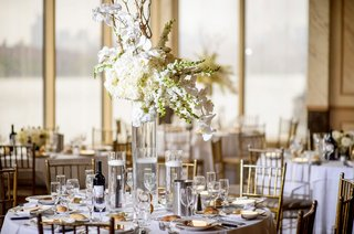 tall-glass-centerpiece-with-hydrangeas-orchids-and-branches-with-floating-candles-on-either-side