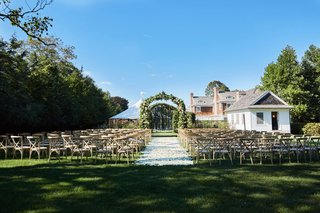 wedding-ceremony-on-grass-lawn-wood-vineyard-x-back-chairs-white-flower-petal-aisle-greenery-arch