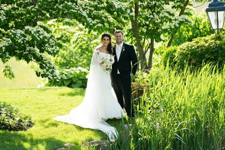 bride-and-groom-in-grass-field-next-to-pond