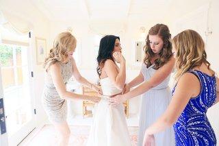 mother-of-the-bride-and-bridesmaids-help-bride-into-monique-lhuillier-crop-top-dress