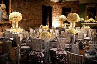 reception-room-with-brick-wall-paintings-and-silver-tables-with-white-centerpieces