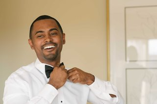 african-american-groom-getting-ready-for-wedding-in-grooms-lounge