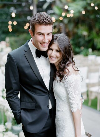 groom-in-black-and-white-tuxedo-with-bow-tie-smiling-with-bride-in-marchesa-wedding-dress