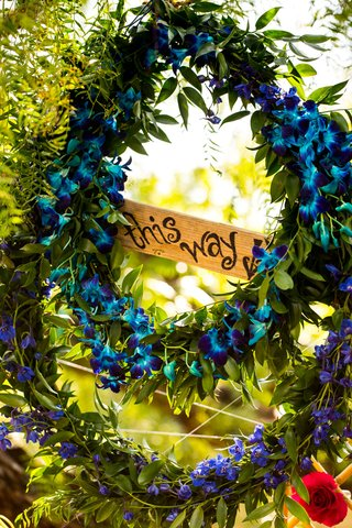 wreath-of-dyed-blue-orchids-surround-sign-reading-this-way-with-arrow-alice-in-wonderland-inspira