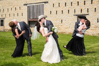 groom-dipping-bride-in-kiss-with-parents-doing-same-thing