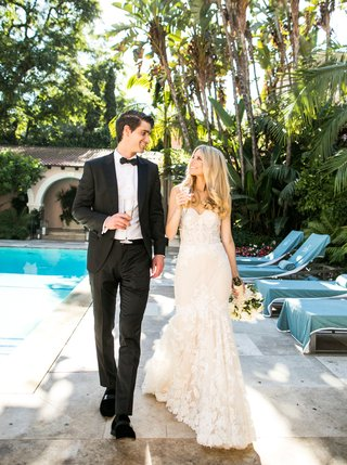 wedding-portrait-bride-and-groom-at-hotel-bel-air-pool-with-flute-of-champagne-california-wedding