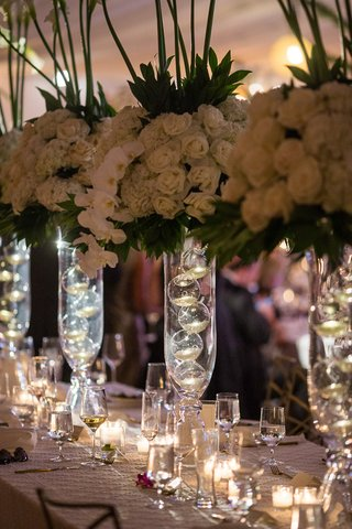 wedding-reception-centerpieces-florals-on-glass-stands-with-glass-bulbs-ivory-roses-orchids