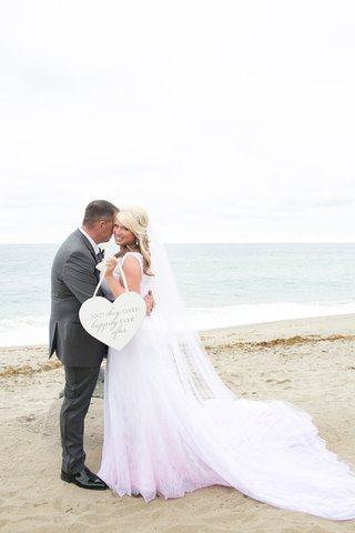 bride-and-groom-on-beach-with-heart-shaped-sign