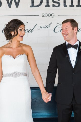 bride-and-groom-hold-hands-and-smile-at-each-other-in-white-dress-and-tuxedo