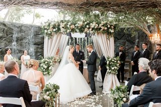 calamigos-ranch-wedding-ceremony-in-front-of-waterfall-groom-reads-vows