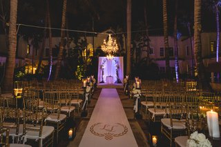 aisle-runner-with-monogram-and-violet-light-at-altar-palm-trees-chandelier-gold-chairs