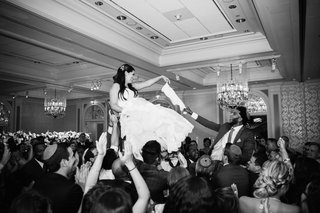 black-and-white-photo-of-bride-and-groom-lifted-in-chairs-jewish-reception-tradition