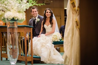 bride-and-groom-sit-down-at-church-ceremony