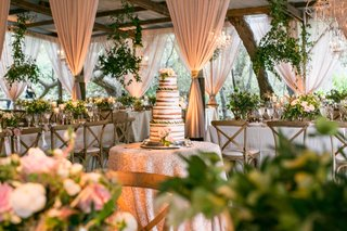 naked-cake-with-fresh-flowers-in-center-of-barn-venue-blush-drapery-chandeliers-foliage