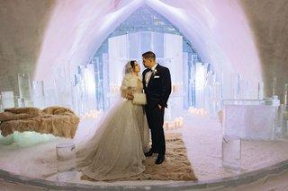 bride-and-groom-portrait-ice-castle-wedding-chapel-snow-floor-faux-fur-rugs-throws