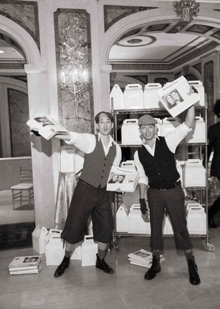 black-and-white-photo-of-newsboys-passing-out-special-editions-of-new-york-times-newspapers-at-end