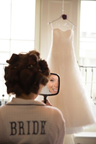bride-with-hair-in-curlers-looking-in-handheld-mirror-in-white-robe-embroidered-with-bride-vera-wang
