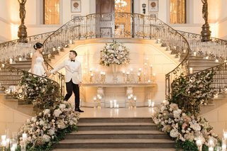 bride-and-groom-walking-down-together-grand-staircase-oheka-castle-flowers-and-candles-on-staircases