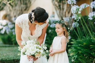 bride-with-headpiece-and-lace-wedding-dress-white-bouquet-with-flower-girl-in-green-flower-crown