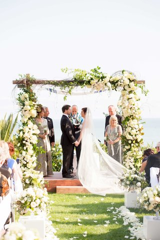 couple-exchanges-vows-under-wooden-chuppah-cathedral-veil-black-tuxedo-jewish-wedding-white-flowers