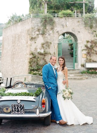 wedding-getaway-car-italy-license-plate-garland-just-married-banner-sign-groom-in-blue-suit-bride