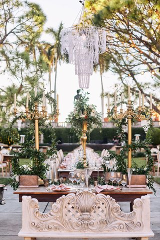sweetheart-table-with-carved-bench-three-tall-gold-candelabra-with-greenery-chandelier-above