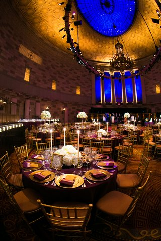 purple-wedding-table-with-gold-chargers-and-tall-taper-candle-centerpieces