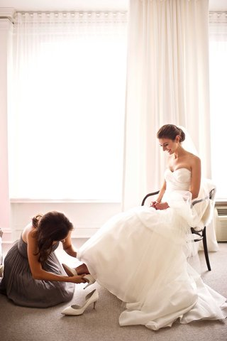 bride-in-strapless-monique-lhuillier-gown-having-bridesmaid-help-put-on-white-wedding-shoes