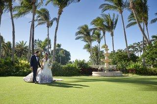 bride-in-purple-floral-romona-keveza-wedding-dress-groom-in-navy-tuxedo-palm-trees